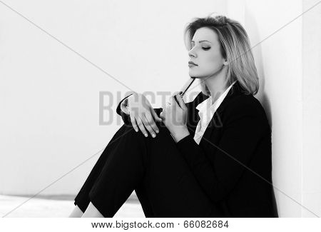 Sad fashion woman sitting at the wall