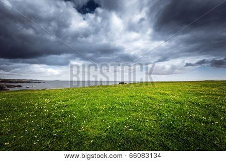 Beautiful coastal landscape with a green meadow and the ocean on a stormy weather