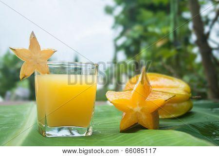 Starfruit and juice on a banana leaf.