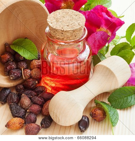 Essential Oil In Glass Bottle, Dried Rose-hip Berries In Wooden Mortar And Rose Hip Flowers