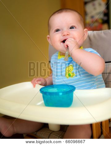 Happy baby infant boy eating meal while sitting in high chair