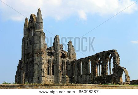 Scenic view of the ruins of Whitby Abbey with blue sky and cloudscape background.