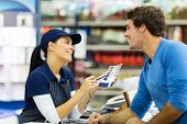 stock photo of over counter  - female paint store worker talking to customer over the counter - JPG