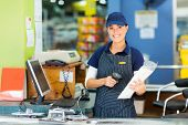 stock photo of apron  - attractive female cashier at hardware store - JPG