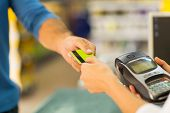 image of debit card  - customer paying with credit card at supermarket - JPG