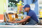 foto of cashiers  - happy african male cashier working at till point in supermarket - JPG