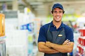 stock photo of hardware  - happy young salesman standing in hardware store - JPG