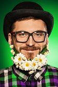 stock photo of bowler  - Funny young man with a beard of flowers wearing elegant bowler hat and glasses - JPG