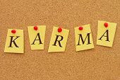 foto of karma  - Karma Four yellow notes on a cork board with the word Karma - JPG