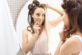 stock photo of rectifier  - Woman with hair standing in front of a mirror - JPG