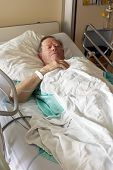 stock photo of intensive care unit  - Senior man lying in hospital bed getting oxygen in intensive care unit vertical