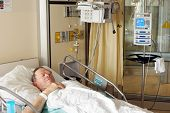 picture of intensive care unit  - Senior man lying in hospital bed getting oxygen in intensive care unit