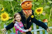 picture of scarecrow  - Scarecrow and happy girl  in the garden - JPG