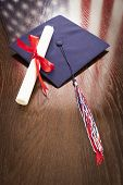 picture of tassels  - Graduation Cap with Tassel and Diploma Wresting on Wooden Table with American Flag Reflection - JPG