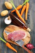 stock photo of duck breast  - Duck breast on a cutting board vegetables and spices - JPG