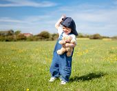 picture of dungarees  - A Baby Girl In Dungarees With A Soft Toy In Her Hands Walking In The Field - JPG