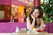 stock photo of ice cream parlor  - Young woman in a cafe or ice cream parlor eating a cake and using her phone - JPG