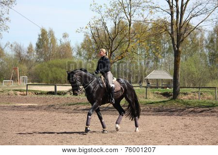 Blonde Woman Riding Black Horse