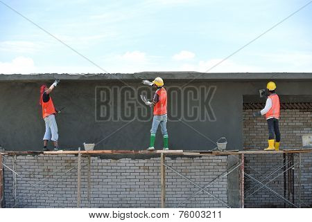 Group of construction workers plastering wall
