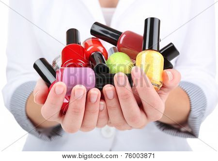 Colorful nail polishes in hands, close-up