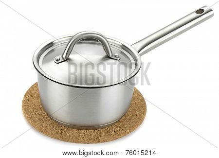 Stainless steel saucepan over cork trivet isolated on white background.