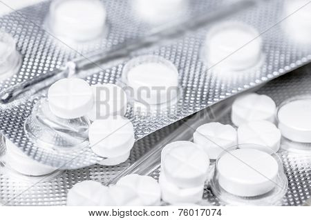 Close up of medicine white tablets in the blister and thermometer on a wooden table