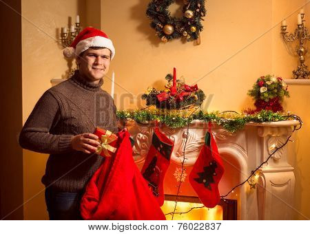 Smiling Man Putting Presents In Christmas Stockings Hanging On Fireplace