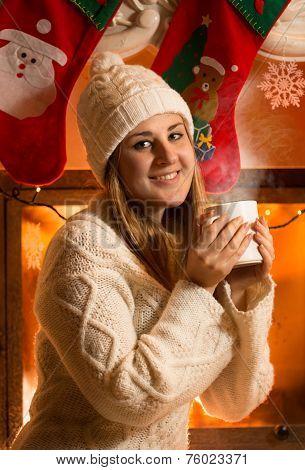 Portrait Of Beautiful Woman In Woolen Sweater Drinking Tea At Fireplace