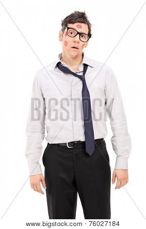 Confused man with many lipstick kisses on his face isolated on white background