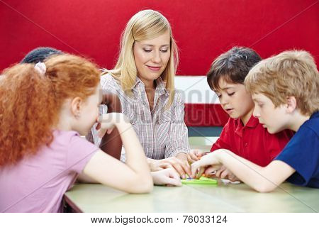 Students playing with teacher in elementary school class