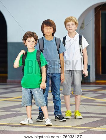 Three children in a row in elementary school on a schoolyard
