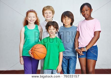 Smiling group of children in elementary school with basketball