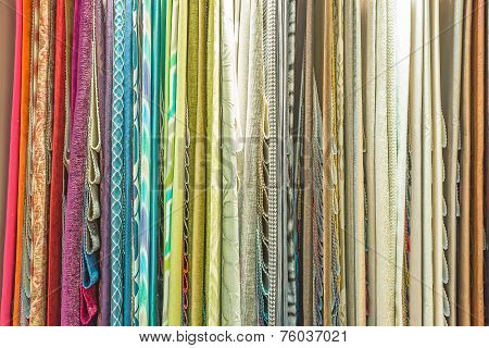 Colorful Curtain Samples Hanging From Hangers On A Rail In A Display In A Retail Store