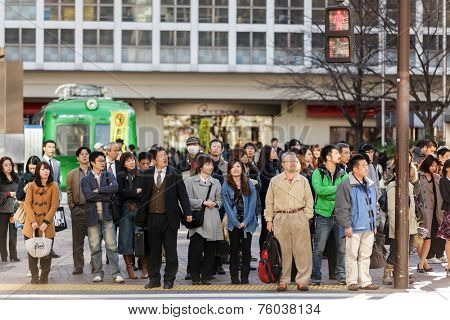 KYOTO, JAPAN, NOVEMBER 25, 2011: Pedestrians are waiting at the crosswalk in the Shibuya district in Tokyo, Japan
