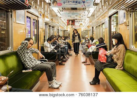 OSAKA, JAPAN, NOVEMBER 15, 2011: People are sitting after work inside a modern and clean train of the Japanese subway in Osaka, Japan.