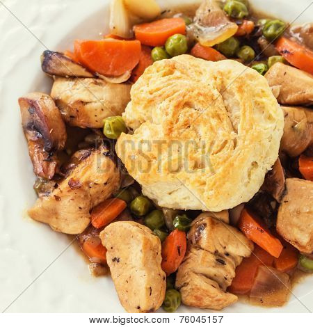 A homemade version of chicken pot pie with a biscuit topping.