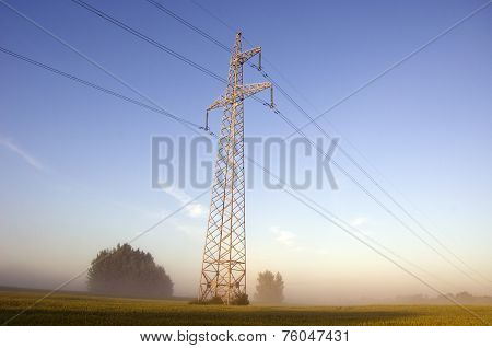 High Voltage Post.high-voltage Tower On Farm Field In Mist