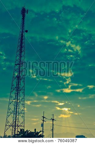 Communication Antenna Tower And Cloudy Sky With Sunbeam