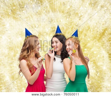 holidays, people and celebration concept - smiling women in party caps blowing to whistles over yellow lights background