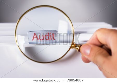 Hand Showing Audit Tab Through Magnifying Glass