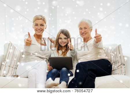 family, generation, technology and people concept - smiling mother, daughter and grandmother with tablet pc computer sitting on couch and showing thumbs up gesture at home