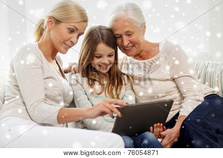 family, generation, technology and people concept - smiling mother, daughter and grandmother with tablet pc computer sitting on couch at home