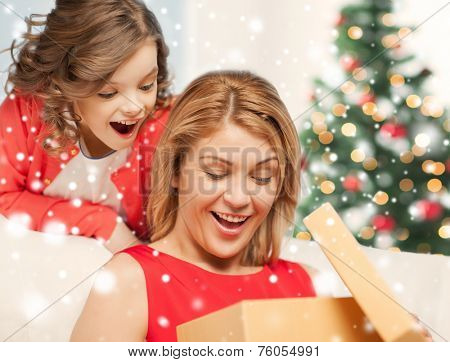 christmas, holidays, people and family concept - smiling mother and daughter opening gift box and getting surprised at home