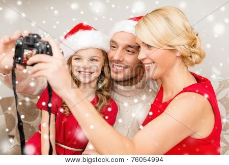 christmas, holidays, technology and people concept - happy family with digital camera taking selfie at home