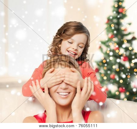 people, motherhood, family, christmas and adoption concept - happy mother and daughter playing and having fun at home