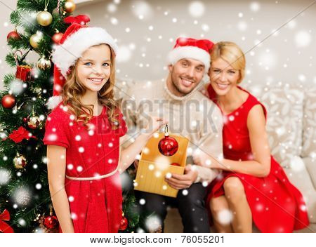 family, christmas, winter holidays, childhood and people concept - smiling family in santa helper hats decorating christmas tree at home
