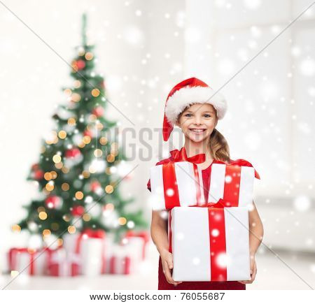 holidays, childhood and people concept - smiling girl in santa helper hat with many gift boxes over living room with christmas tree and snow background
