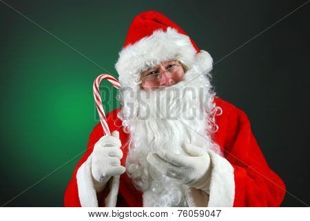 Santa Claus hold a Fresh Candy Cane while against a green background. Candy Canes are loved by everyone at Christmas Time around the world. Candy Canes are made with Peppermint flavor. Peppermint