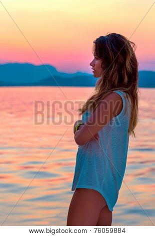 Side view of cute girl enjoying beautiful red and yellow sunset over sea, spending evening on the beach, freedom and enjoyment concept