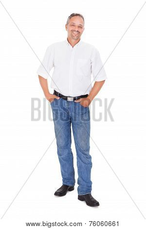 Smiling mature man standing with hands in pockets